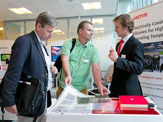 Electronics expert Nicholas Havemann (right) explains the advantages of electrically conductive adhesives for temperature sensitive components in vehicles to two interested customers.